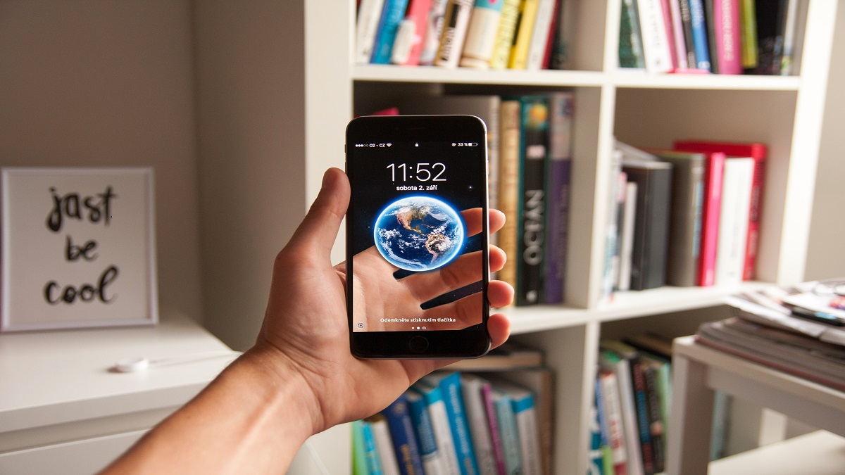 Image of smartphone with a virtual transparent screen showing a globe in a person's hand