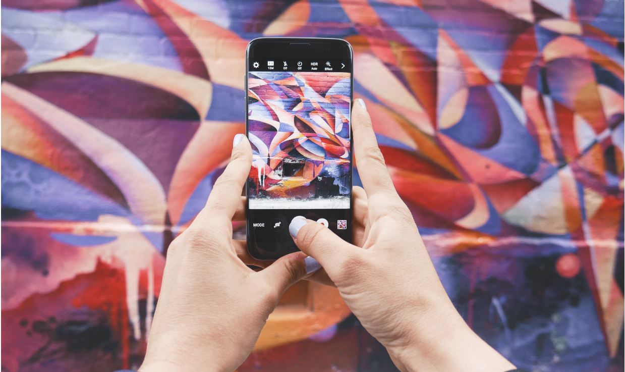 Image of a Instagram influencer taking a photo on her phone of a wall mural