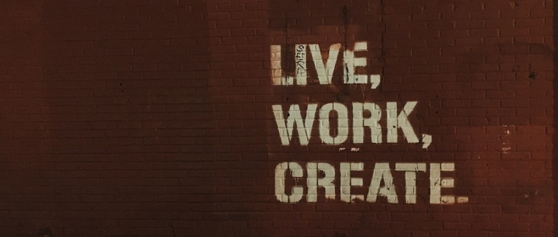 What is marketing image. Image of brick wall with Live, Work, Create written on it.